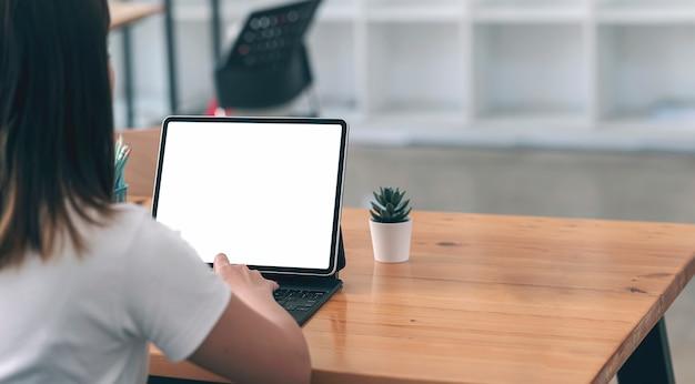 Image Gros Plan De La Jeune Femme Travaillant Sur La Tablette Tactile Alors Qu'il était Assis à La Table Dans L'espace De Travail. Photo Premium