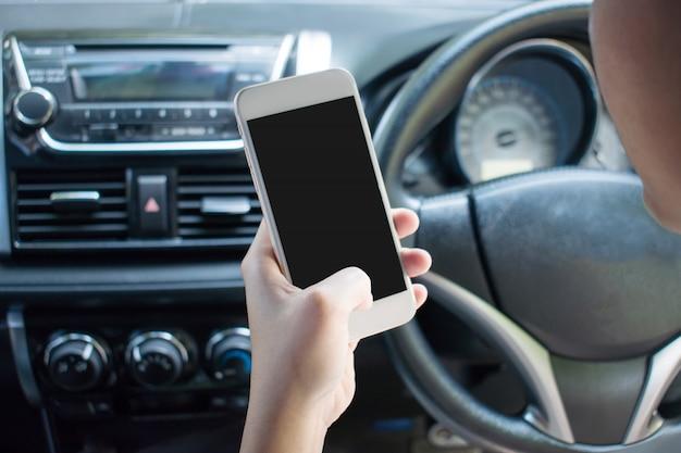 Image Gros Plan D'une Main à L'aide D'un Smartphone Sur Une Voiture En Conduisant Photo Premium