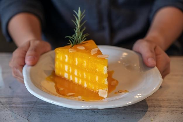 Image Gros Plan Des Mains Tenant Et Montrant Un Morceau De Gâteau Orange Sur Une Plaque En Céramique Au Café Photo Premium