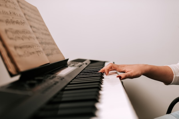Image gros plan d'une musicienne jouant du piano à partir de partitions. Photo Premium
