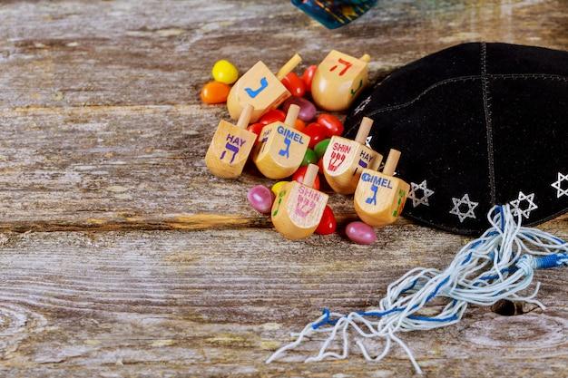 Image de hanoucca de vacances juive avec dreidel en bois tournant sur le fond de paillettes Photo Premium