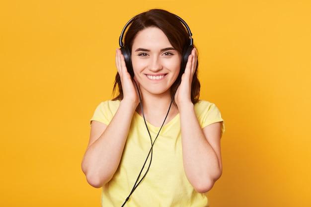 Image De Jeune Femme Heureuse Avec Un Casque D'écoute De La Musique Isolée Sur Jaune Photo gratuit