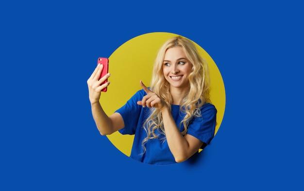 Image De Jeune Femme Heureuse, Debout Sur Un Mur Bleu. Femme Peep Hors D'un Trou Dans Le Mur. Regardant Sur Le Côté Pour Prendre Un Selfie Sur Le Téléphone Mobile. Photo Premium