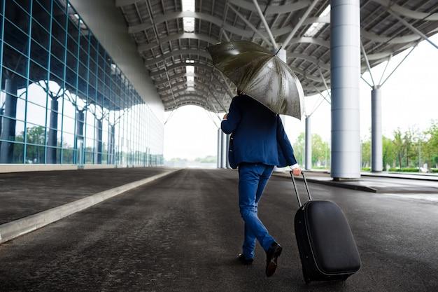 Image - Jeune, Homme Affaires, Tenue, Valise, Et, Parapluie, à, Pluvieux, Aéroport Photo gratuit