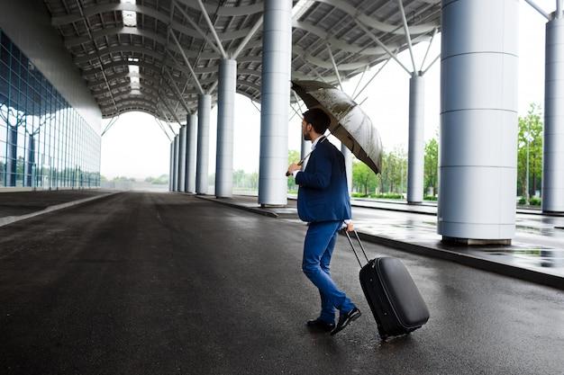 Image - Jeune, Homme Affaires, Tenue, Valise, Et, Parapluie, à, Pluvieux, Terminal Photo gratuit