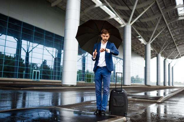Image - Jeune, Homme Affaires, Tenue, Valise, Et, Parapluie, Regarder Montre, Attente, à, Pluvieux, Station Photo gratuit