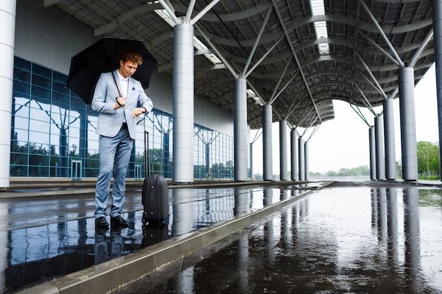 Image - Jeune, Rousse, Homme Affaires, Tenue, Parapluie Noir, Dans, Pluie, Et, Regarder Montre, à, Station Photo gratuit