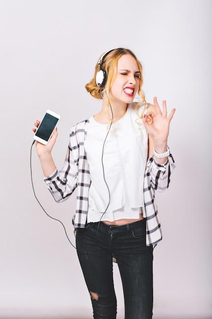 Image D'une Jolie Fille Joyeuse Ravie, écoutant De La Musique Et Profitant Tellement De Sa Vie Passionnante. Humeur Heureuse Et Positive. Corps Mince. Visage Satisfait. émotions Vives. Photo gratuit
