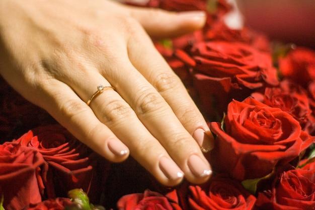 Image d'une main de femme avec une bague de mariage sur des roses Photo Premium