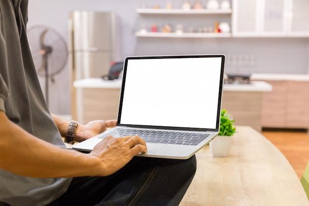 Image de la maquette d'un homme d'affaires utilisant un ordinateur portable avec un écran de bureau blanc vierge à la maison Photo Premium