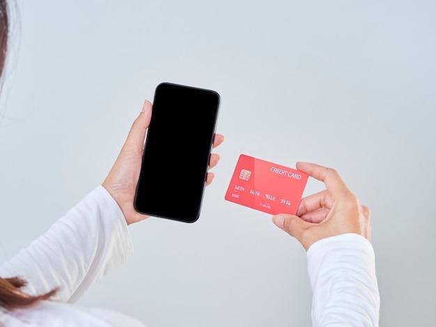 Image De Maquette De Main De Femme Tenant Un Téléphone Mobile, écran Blanc Et Carte De Crédit Sur Fond Gris Photo Premium