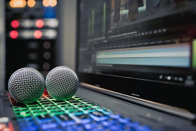 Une image de microphone en gros plan est placée sur le portable avec un clavier rétro-éclairé dans la salle de contrôle. Photo Premium