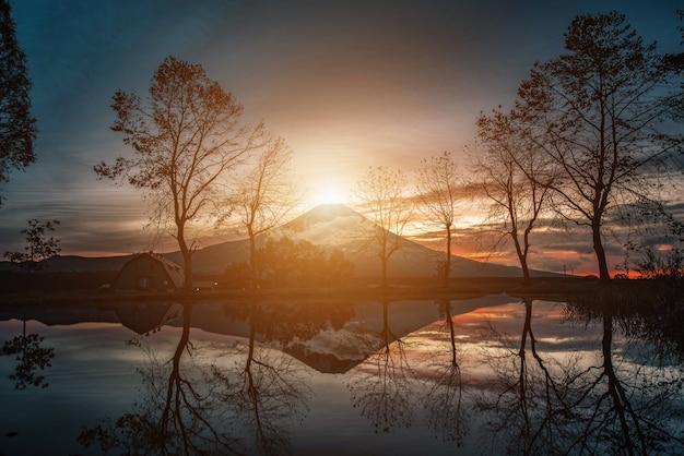 Image de paysages de la montagne fuji avec de grands arbres et un lac au lever du soleil dans le camp de fumotopara, fujinomiya, japon. Photo Premium