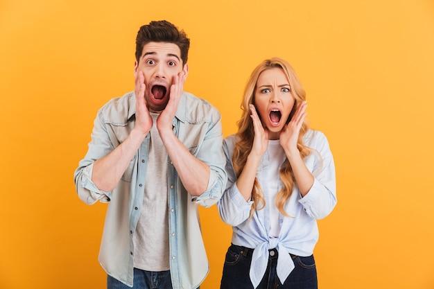 Image De Personnes Choquées Homme Et Femme En Vêtements De Base Exprimant La Surprise Ou La Peur Avec La Bouche Ouverte, Isolé Sur Mur Jaune Photo Premium