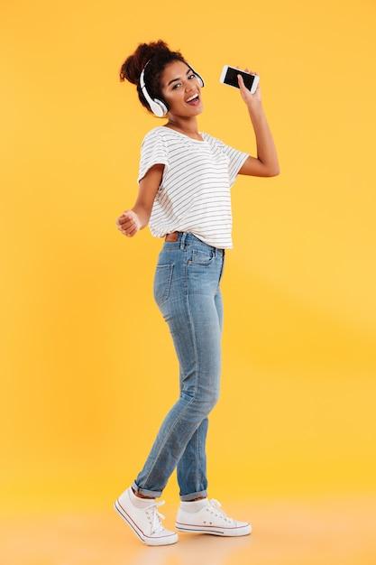 Image Pleine Longueur De Femme Africaine Heureuse Dansant Et écoutant De La Musique Photo gratuit