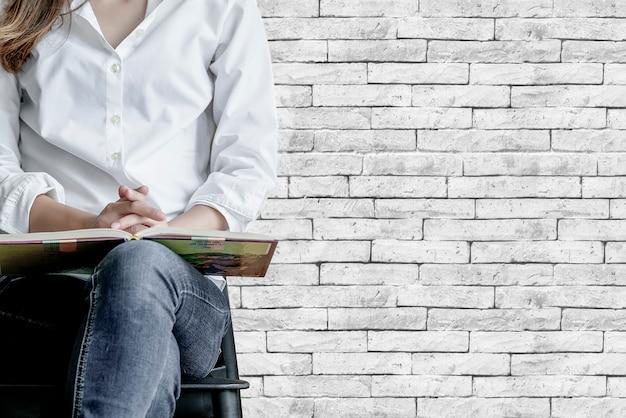 Image recadrée de femme avec livre assis sur une chaise avec vieux mur de briques Photo Premium