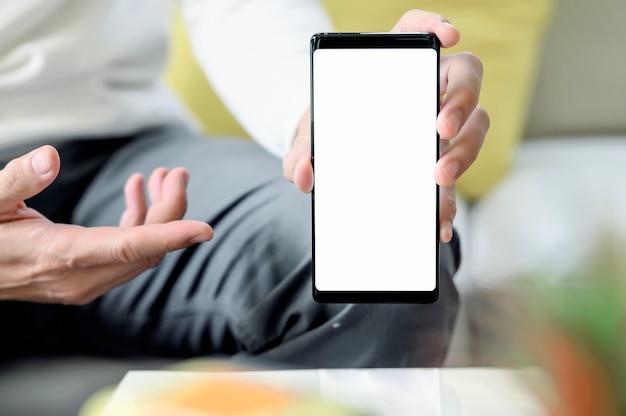 Image recadrée d'un homme tenant et montrant un écran vide de smartphone assis à la maison Photo Premium
