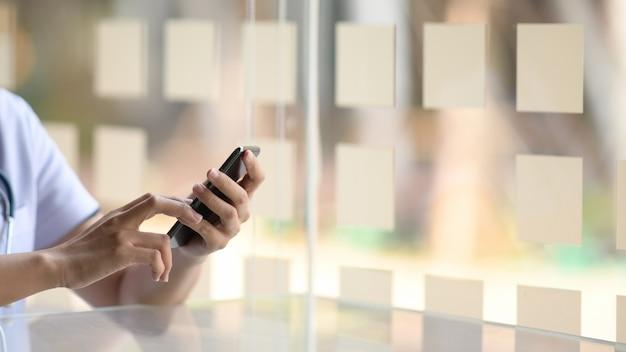 Image recadrée de médecin à l'aide de téléphone portable dans les mains au bureau Photo Premium