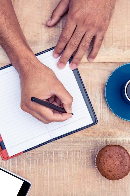 Image recadrée de la personne qui écrit sur le journal à la table Photo Premium