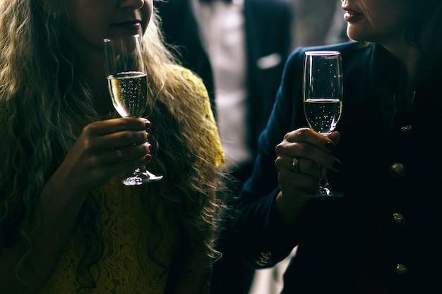 Image sombre de femmes parlant et de flûtes à champagne dans leurs bras Photo gratuit