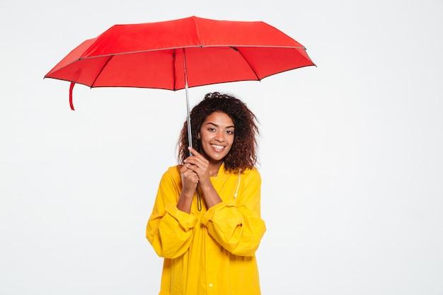 Image - Sourire, Femme Africaine, Dans, Imperméable, Cacher, Sous, Parapluie, Sur, Blanc Photo gratuit