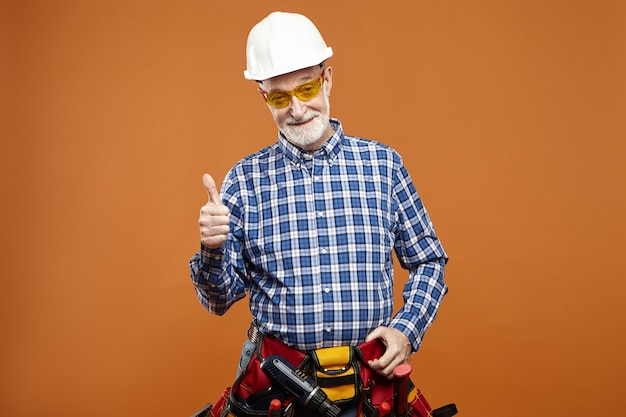 Image De Studio De Joyeux Réparateur Barbu âgé Senior Heureux Portant Un Casque Photo gratuit