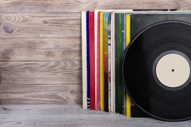Image de style rétro d'une collection de disques de vinyle lp avec manches sur un fond en bois. Photo Premium