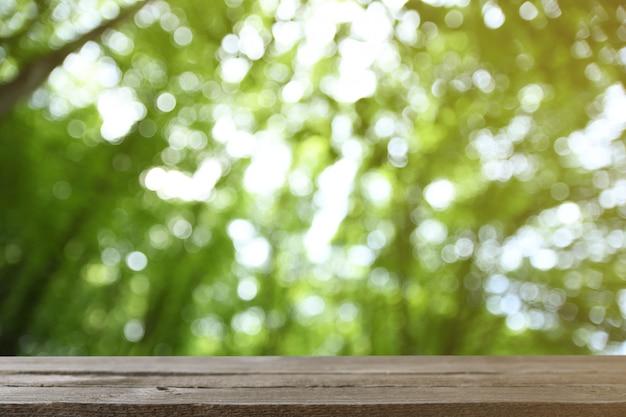 Image de table en bois gris en face d'arbres natureof floue abstraite sur un pré vert Photo Premium