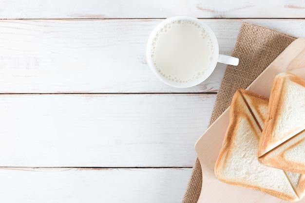 Image vue de dessus du pain cuit au four et du pain en tranches avec du lait chaud dans une tasse blanche sur une table en bois blanc, petit déjeuner le matin, frais fait maison, espace de copie Photo Premium