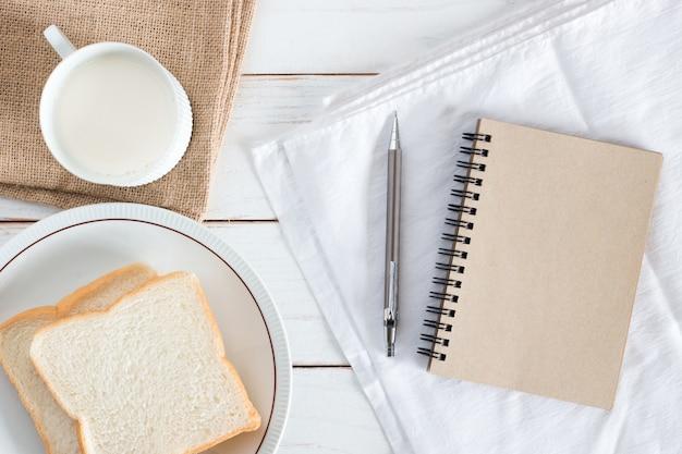 Image vue de dessus du pain en tranches sur plat avec du lait chaud, un crayon et un cahier de papier brun sur une table en bois blanc, petit déjeuner le matin, frais fait maison, espace de copie Photo Premium