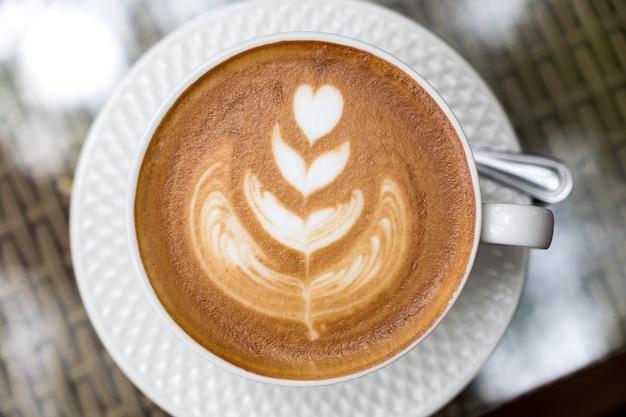 Image vue de dessus d'une tasse de café au lait chaud avec de l'art latte sur table Photo Premium