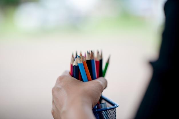 Images de main et crayon, couleur de fond vert concept de l'éducation Photo Premium