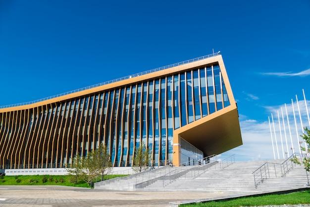 Immeuble de bureaux dans le pré avec des fenêtres en verre qui reflètent les nuages flottants, le long du bâtiment il y a des gens Photo Premium