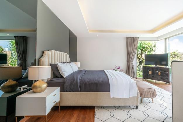Immobilier design d'intérieur de luxe dans la chambre de la villa avec piscine et lit king confortable. Photo Premium