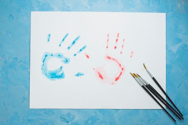 Impression de main bleue et rouge sur une feuille blanche avec un pinceau sur fond bleu Photo gratuit