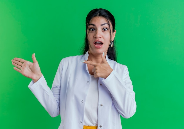 Impressionné Jeune Femme Médecin Portant Une Robe Médicale à La Recherche Montrant La Main Vide Et Pointant Vers Elle Photo gratuit