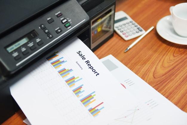 Imprimante imprimant des rapports d'activités sur la vente et sur la pile de documents Photo Premium