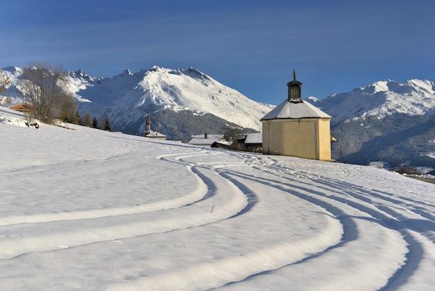 Imprimé de ski de fond allant à une petite chapelle dans un magnifique paysage de montagne enneigée Photo Premium