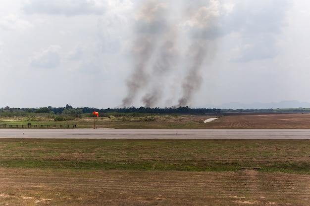 Un incendie brûle près de l'aéroport avec de la fumée qui provoque une mauvaise pollution. Photo Premium