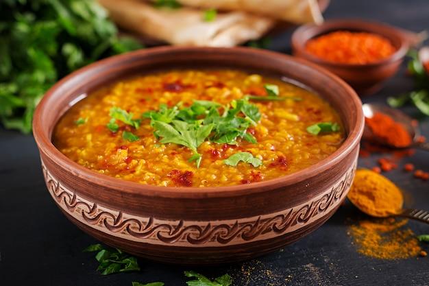 Indian Dhal Curry épicé Dans Un Bol, épices, Herbes, Fond En Bois Noir Rustique. Photo Premium