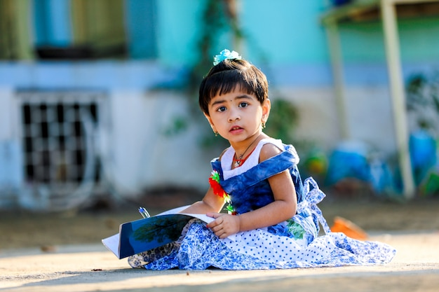 Indian little girl enfant écrit sur le carnet de notes, étudiant Photo Premium