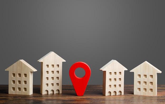 Un Indicateur D'emplacement Rouge Se Dresse Entre Les Bâtiments Résidentiels. Photo Premium