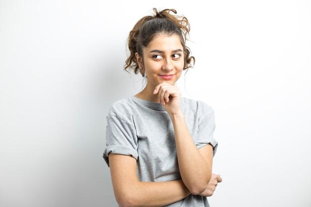 Indienne pensive sur un fond blanc. penser à l'idée d'une jeune femme souriante Photo Premium