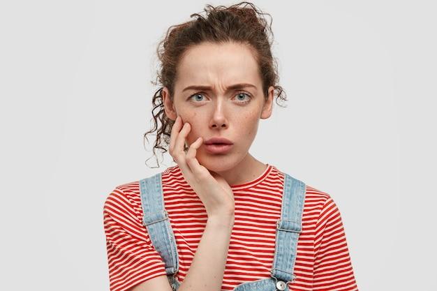 Indigné De Taches De Rousseur Jeune Femme Posant Contre Le Mur Blanc Photo gratuit