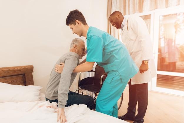 L'infirmière aide le vieil homme à se lever du lit. Photo Premium