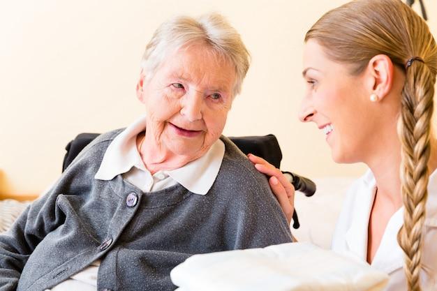Infirmière apportant des fournitures à une femme dans une maison de retraite Photo Premium