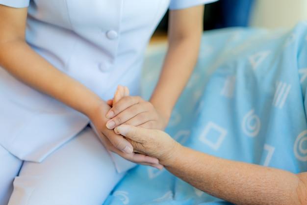 Infirmière assise sur un lit d'hôpital à côté d'une femme âgée Photo Premium