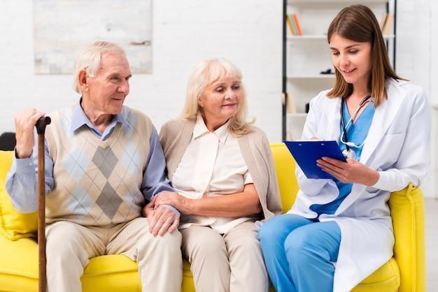 Infirmière assise avec vieil homme et femme sur un canapé Photo gratuit