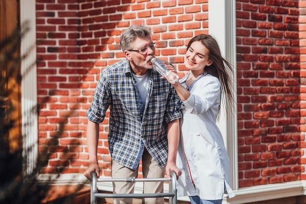 Infirmière attrayante avec homme senior, lui donnant de l'eau Photo Premium
