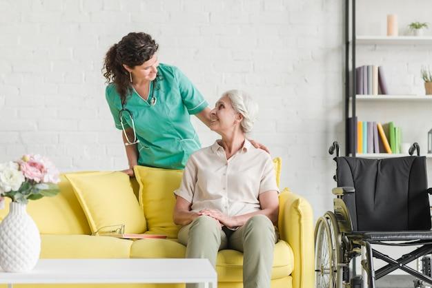Infirmière consoler son patient senior assis sur le canapé Photo gratuit